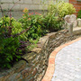 stone seat and raised beds (Skimmia japonica (Skimmia))