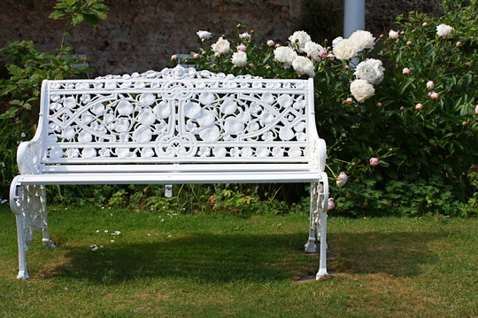 Seat and peonies in white garden, Greys Court