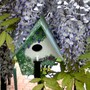 This is my bird house nestling in the Wisteria flowers.