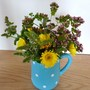 Yellow Gerbera with Mint and Marjoram in a small jug.