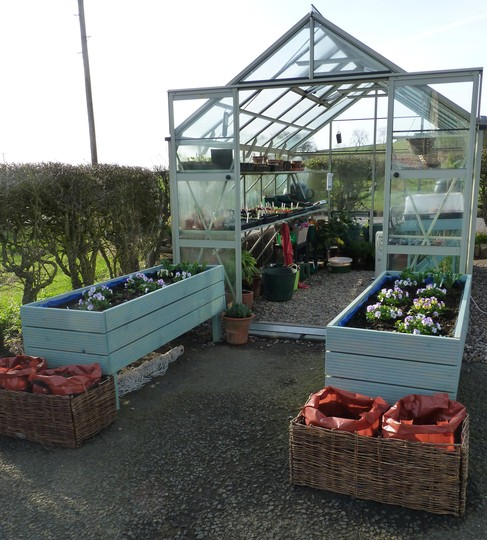 Greenhouse with planters outside.