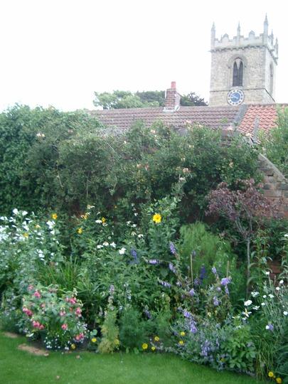 All Saints church behind the garden wall.