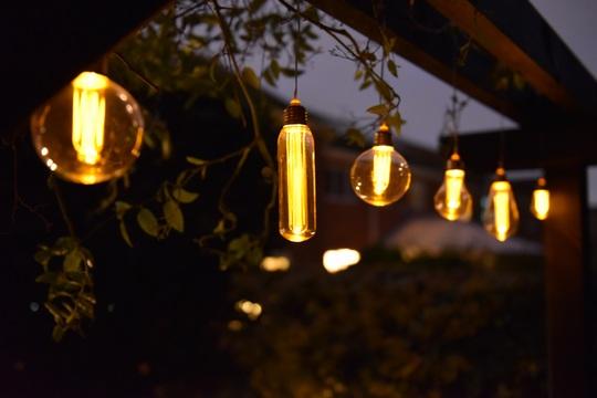 Garden Solar lights hanging from pergola.