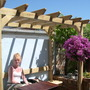 Jan enjoying the sun in our back garden (bougainvillea)