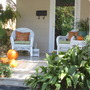 White bungalow with pumpkins.