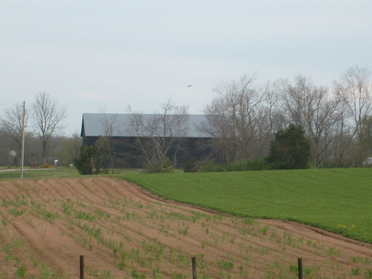 Blue barn and plowed field.